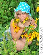 Купить «Девушка с цветами рудбекии в саду», эксклюзивное фото № 6585361, снято 23 июля 2011 г. (c) Юрий Морозов / Фотобанк Лори