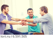 Купить «smiling male friends with hands together at home», фото № 6591505, снято 22 марта 2014 г. (c) Syda Productions / Фотобанк Лори