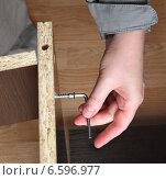 Купить «Сборка мебели ручным инструментом. Торцевой шестигранный мебельный ключ крупным планом в руке закручивает шуруп в древесно-стружечные панели», фото № 6596977, снято 21 октября 2014 г. (c) Владимир Григорьев / Фотобанк Лори