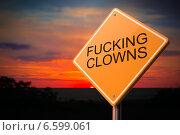 Fucking Clowns, надпись на дорожном знаке на фоне вечернего неба. Стоковое фото, фотограф Илья Урядников / Фотобанк Лори