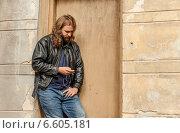 Длинноволосый и бородатый мужчина в кожаной куртке слушает музыку, прислонившись к стене здания (2014 год). Стоковое фото, фотограф Ilie-Cristian IONESCU / Фотобанк Лори