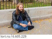 Длинноволосый бородатый мужчина наслаждается музыкой в парке в наушниках, сидя на асфальте (2014 год). Стоковое фото, фотограф Ilie-Cristian IONESCU / Фотобанк Лори