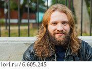 Бородатый мужчина с длинными волосами в черной кожаной куртке слушает музыку в парке в наушниках (2014 год). Стоковое фото, фотограф Ilie-Cristian IONESCU / Фотобанк Лори