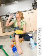 Купить «A woman drinking water sitting near cleaning accessories on the kitchen floor.», фото № 6617429, снято 22 сентября 2019 г. (c) BE&W Photo / Фотобанк Лори