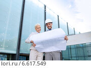 Купить «smiling businessmen with blueprint and helmets», фото № 6617549, снято 19 августа 2014 г. (c) Syda Productions / Фотобанк Лори