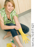 Купить «A smiling woman putting on a plastic glove sitting on the kitchen floor.», фото № 6617621, снято 23 февраля 2019 г. (c) BE&W Photo / Фотобанк Лори