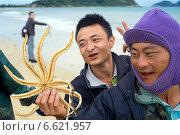 Два весёлых китайца предлагают купить морскую звезду (2014 год). Редакционное фото, фотограф Алексей Маринченко / Фотобанк Лори