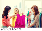 Купить «three smiling friends trying on some clothes», фото № 6627121, снято 12 апреля 2014 г. (c) Syda Productions / Фотобанк Лори