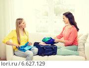Купить «two smiling teenage girls packing suitcase at home», фото № 6627129, снято 12 апреля 2014 г. (c) Syda Productions / Фотобанк Лори