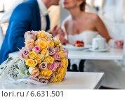 Свадебный букет лежит на столе на фоне поцелуя жениха и невесты, эксклюзивное фото № 6631501, снято 20 сентября 2014 г. (c) Игорь Низов / Фотобанк Лори