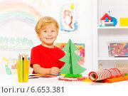 Купить «Мальчик делает ёлку из цветной бумаги», фото № 6653381, снято 26 октября 2014 г. (c) Сергей Новиков / Фотобанк Лори