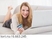 Купить «Blonde shopping online lying on the couch», фото № 6663245, снято 22 августа 2014 г. (c) Wavebreak Media / Фотобанк Лори