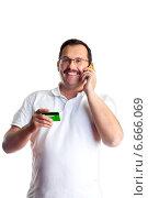 Мужчина говорит по телефон и держит банковскую карту. Стоковое фото, фотограф Татьяна Белова / Фотобанк Лори