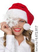 Красивая девушка в шапке Санта Клауса со снежинкой в руках. Стоковое фото, фотограф Заметалов Андрей / Фотобанк Лори