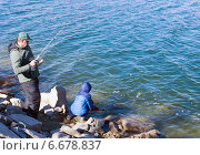 Купить «Отец с сыном ловят форель в озере. Взрослый поймал рыбу и заводит ее в сачок, который держит ребенок», фото № 6678837, снято 16 ноября 2014 г. (c) Ирина Кожемякина / Фотобанк Лори