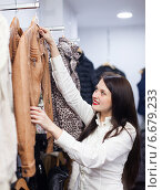 Купить «Cute woman choosing jacket at clothing store», фото № 6679233, снято 28 января 2014 г. (c) Яков Филимонов / Фотобанк Лори