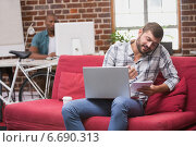 Man using laptop and mobile phone on couch in office. Стоковое фото, агентство Wavebreak Media / Фотобанк Лори