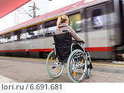 woman sitting in a wheelchair on a train station. Стоковое фото, фотограф Erwin Wodicka / Фотобанк Лори