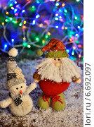 Игрушечный снеговик и дед Мороз на фоне горящей гирлянды. Новый год. Стоковое фото, фотограф Владимир Ковальчук / Фотобанк Лори