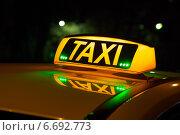 Купить «Горящая надпись TAXI с зелеными огоньками на крыше автомобиля», фото № 6692773, снято 20 ноября 2014 г. (c) Родион Власов / Фотобанк Лори