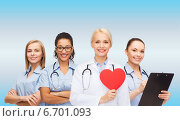 Купить «smiling female doctor and nurses with red heart», фото № 6701093, снято 1 декабря 2013 г. (c) Syda Productions / Фотобанк Лори