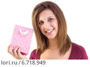 Купить «Young woman holding a pink gift bag smiling at camera», фото № 6718949, снято 11 июля 2014 г. (c) Wavebreak Media / Фотобанк Лори