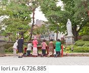 Купить «Корейские женщины молятся статуе Девы Марии во дворе кафедрального собора Мёндон (Собор Непорочного Зачатия Пресвятой Девы Марии) в Сеуле, Южная Корея», фото № 6726885, снято 28 сентября 2014 г. (c) Иван Марчук / Фотобанк Лори