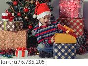 Счастливый мальчик открывает новогодние подарки возле елки. Стоковое фото, фотограф Сергей Богданов / Фотобанк Лори