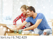 smiling couple opening cardboard box with dishes. Стоковое фото, фотограф Syda Productions / Фотобанк Лори