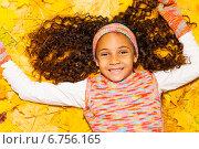 Купить «Портрет счастливой темнокожей девочки с длинными кудрявыми волосами, лежащей на осенних листьях», фото № 6756165, снято 19 октября 2014 г. (c) Сергей Новиков / Фотобанк Лори