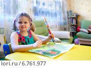 Купить «Девочка-левша рисует большим карандашом, сидя за столом», фото № 6761977, снято 29 января 2012 г. (c) Наталья Федорова / Фотобанк Лори