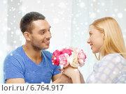Купить «smiling man giving girlfriend flowers at home», фото № 6764917, снято 9 февраля 2014 г. (c) Syda Productions / Фотобанк Лори
