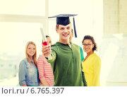 Купить «smiling male student with diploma and corner-cap», фото № 6765397, снято 29 марта 2014 г. (c) Syda Productions / Фотобанк Лори