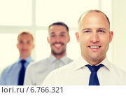 Купить «smiling businessman in office with team on back», фото № 6766321, снято 10 мая 2014 г. (c) Syda Productions / Фотобанк Лори