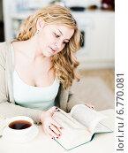 Купить «Красивая девушка с чашкой кофе сидит за столом и листает книгу», фото № 6770081, снято 16 апреля 2014 г. (c) Валерия Потапова / Фотобанк Лори
