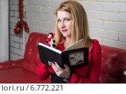 Молодая привлекательная блондинка записывает в тетрадь список подарков на Новый Год (2014 год). Редакционное фото, фотограф Андрей Шарашкин / Фотобанк Лори