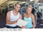 Купить «Woman discussing her performance on clipboard with a trainer at gym», фото № 6782741, снято 27 февраля 2014 г. (c) Wavebreak Media / Фотобанк Лори
