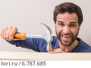 Купить «Casual man hammering his finger by accident», фото № 6787685, снято 5 сентября 2014 г. (c) Wavebreak Media / Фотобанк Лори
