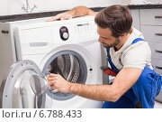 Handyman fixing a washing machine. Стоковое фото, агентство Wavebreak Media / Фотобанк Лори