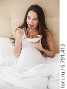 Pregnant brunette eating cereal in bed. Стоковое фото, агентство Wavebreak Media / Фотобанк Лори
