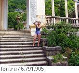 Молодая женщина в голубой футболке и шортах фотографирует на ступеньках колоннады в Гаграх. Абхазия, фото № 6791905, снято 17 августа 2003 г. (c) Евгений Ткачёв / Фотобанк Лори