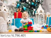 Купить «Маленький мальчик играет разноцветным конструктором на полу на фоне новогодней елки и подарков», фото № 6796401, снято 11 декабря 2014 г. (c) Бандуренко Андрей / Фотобанк Лори