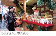Купить «Покупатель у лотка с сувенирами. ГУМ-ярмарка на Красной площади в Москве», эксклюзивное фото № 6797953, снято 13 декабря 2014 г. (c) lana1501 / Фотобанк Лори