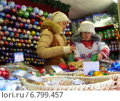 Купить «Продавцы за прилавком с сувенирами. ГУМ-ярмарка на Красной площади в Москве», эксклюзивное фото № 6799457, снято 12 декабря 2014 г. (c) lana1501 / Фотобанк Лори