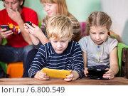 Купить «Семейное времяпровождение за играми в смартфонах», фото № 6800549, снято 7 декабря 2014 г. (c) Кекяляйнен Андрей / Фотобанк Лори