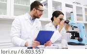 scientists with tablet pc and microscope in lab, видеоролик № 6803557, снято 7 декабря 2014 г. (c) Syda Productions / Фотобанк Лори