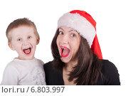 Купить «Женщина в новогодней шапке с ребенком радуются, открыв рот», фото № 6803997, снято 7 декабря 2014 г. (c) Ирина Ткачук / Фотобанк Лори