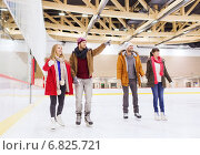 happy friends pointing finger on skating rink. Стоковое фото, фотограф Syda Productions / Фотобанк Лори
