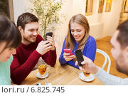 Купить «group of friends with smartphones meeting at cafe», фото № 6825745, снято 26 ноября 2014 г. (c) Syda Productions / Фотобанк Лори