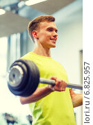 smiling man doing exercise with barbell in gym. Стоковое фото, фотограф Syda Productions / Фотобанк Лори